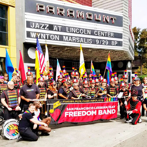 Marching band poses for a group picture in front of the Paramount Theatre in Oakland